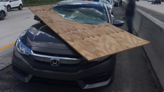 Piece of plywood slices car's windshield, narrowly misses driver