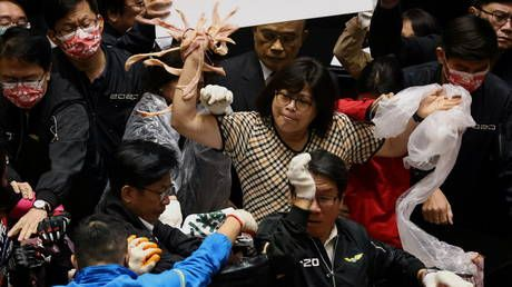 Taiwan lawmakers throw PIG GUTS during parliament session to protest meat imports from US
