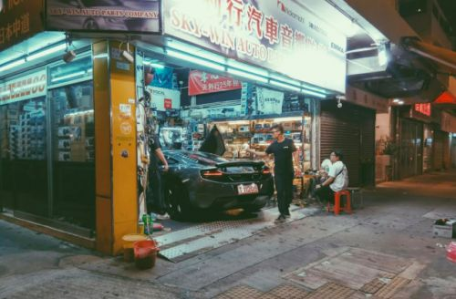 A McLaren MP4-12C being wrenched on in a small audio shop in Yuen Long, Hong Kong