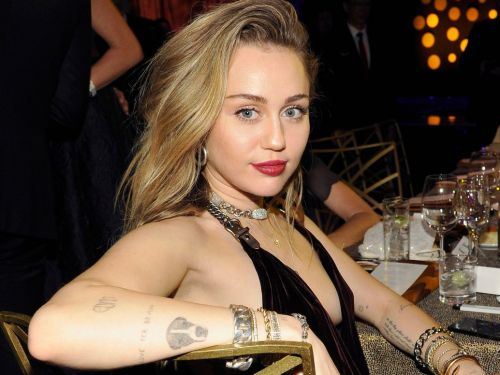 Miley Cyrus turned heads in a $3,430 velvet dress with a plunging V-neck, one of her signature looks