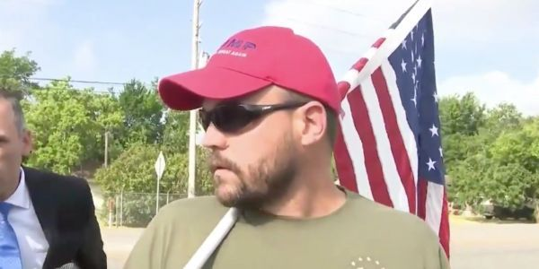 Man in Trump hat prompts confusion by showing up near scene of Texas school shooting with gun and American flag