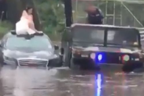 Bride rescued by police officer after car gets stuck in flood waters