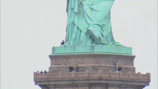 Live video: Woman climbs statue of Liberty in NYC