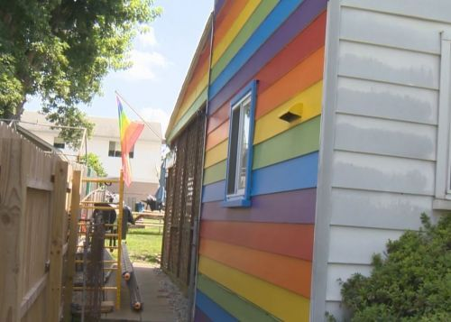 Couple paints LGBT flag on the side of house after neighbors harass them