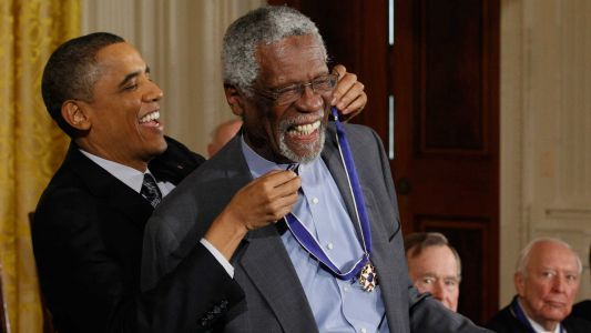 Photo appears to show Bill Russell kneeling with Presidential Medal of Freedom
