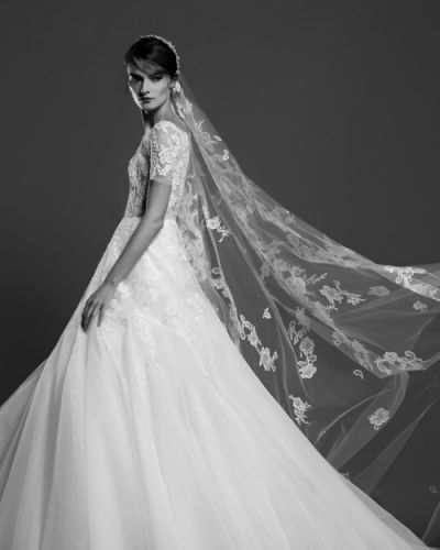 A white tulle bridal gown with a lace bodice and skirt overlay