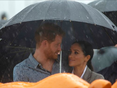 Prince Harry and Meghan Markle shared an umbrella in the rain, and the photos will melt your heart