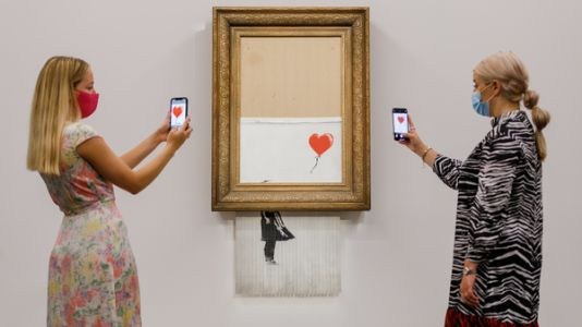 A half-shredded Banksy piece is auctioned for $25.4 million, a record for the artist