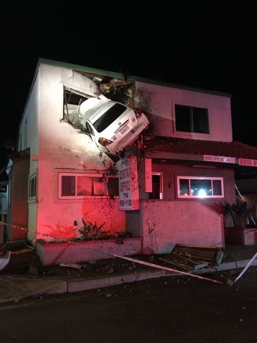 Car goes airborne, crashes into second floor of California office building