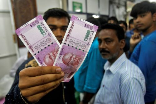 Indian rupee sinks to record low after central bank unexpectedly holds rates