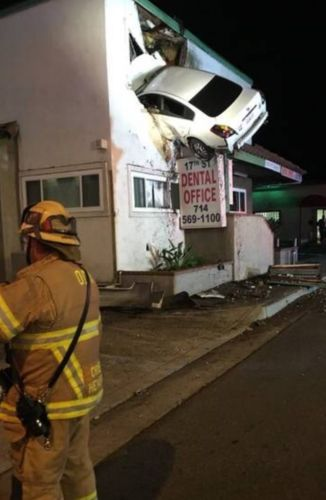 Car goes airborne, gets wedged in upper wall of two-story building